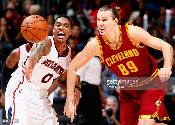Jeff Teague of the Atlanta Hawks knocks the ball away from Lou Amundson of the Cleveland Cavaliers at Philips Arena on December 30 2014 in Atlanta...