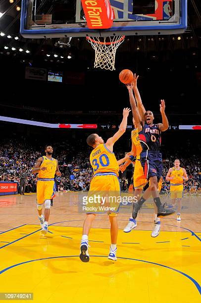 Jeff Teague of the Atlanta Hawks shoots the ball against Andris Biedrins and Stephen Curry of the Golden State Warriors on February 25 2011 at Oracle...