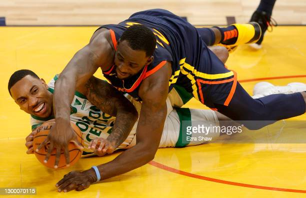 Jeff Teague of the Boston Celtics and Draymond Green of the Golden State Warriors go for a loose ball at Chase Center on February 02, 2021 in San...