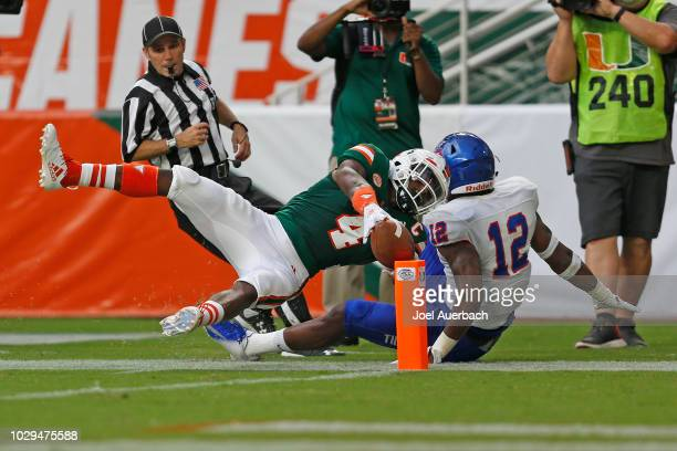 Jeff Thomas of the Miami Hurricanes hits the pylon with the ball to score a touchdown against the Savannah State Tigers before going out of bounds...