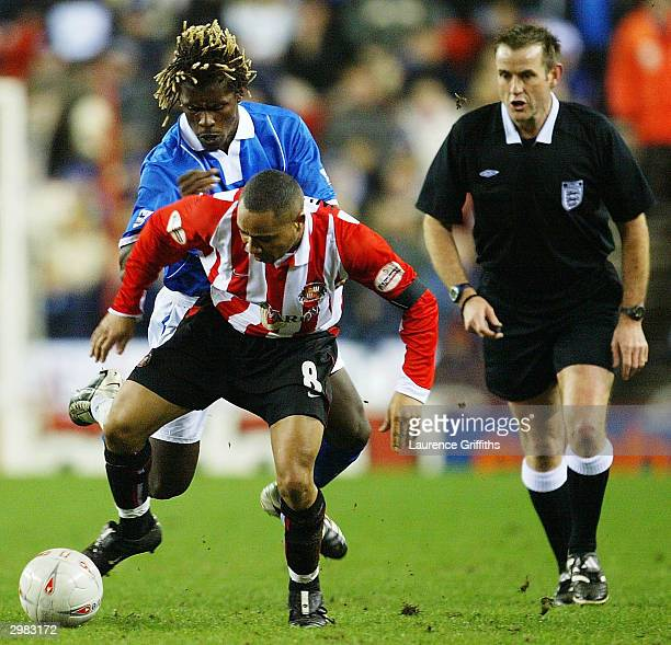 Jeff Whitley of Sunderland is held back by Aliou Cisse of Birmingham during the FA Cup Fifth Round match between Sunderland and Birmingham City at...