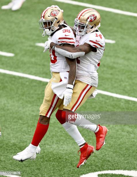 Jeff Wilson Jr. #30 of the San Francisco 49ers is congratulated by teammate Mohamed Sanu after Wilson Jr. Scored a touchdown in the fourth quarter...