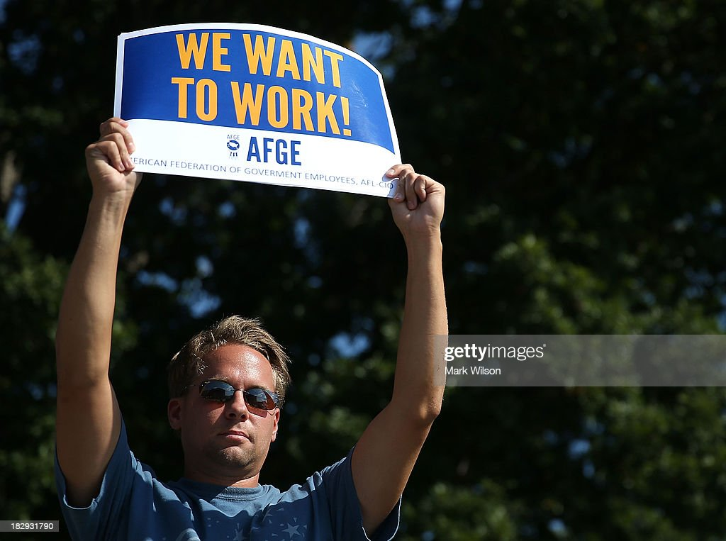 Jeff Wismer holds up a (We Want To Work) sign while listening to U.S. House Minority Leader Rep. Nancy Pelosi (D-CA) speak during a news conference on the federal government shutdown at the U.S. Capitol on October 2, 2013 in Washington, DC. Later today President Barack Obama will meet with congressional leaders at the White House to discuss an end to the government shutdown.