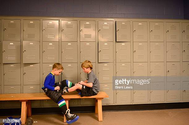 Jeff Witwer helps to tie his brother's Kit skates before the start of practice at Edge Ice Arena on February 17 2016 in Littleton Colorado Hockey has...