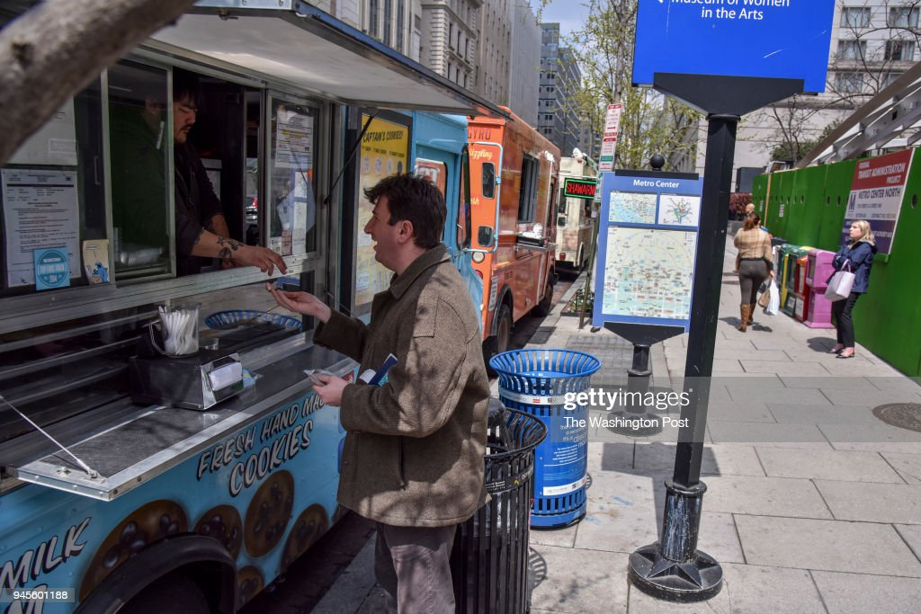Jeff Zeeman, R, buys cookies from truck manager Jeremy Summerville at Captain Cookie food truck on Wednesday, April 11, 2018, in Washington, DC. Kirk Francis, the Founder of Captain Cookie, discusses how revised rules for food trucks are putting a pinch on the business.