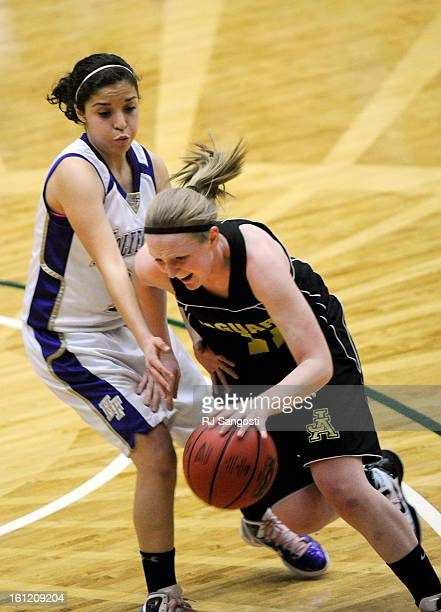 Jefferson Academy's Madison Page right drives around Holy Family's Megan Chavez Friday March 11 during final four action in the 3A girls basketball...