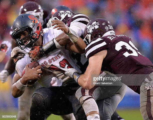 J Jefferson and Richie Brown of the Mississippi State Bulldogs sack Jacoby Brissett of the North Carolina State Wolfpack during the Belk Bowl at Bank...