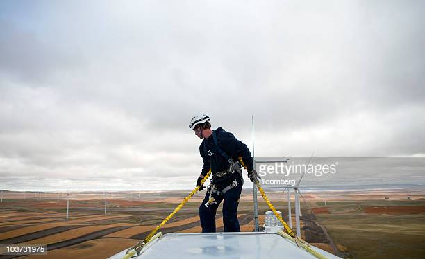 Jefferson Barbee ties on to the nacelle of an Acciona wind turbine at the NaturEner USA LLC Glacier wind energy farm in Ethridge Montana US on Monday...
