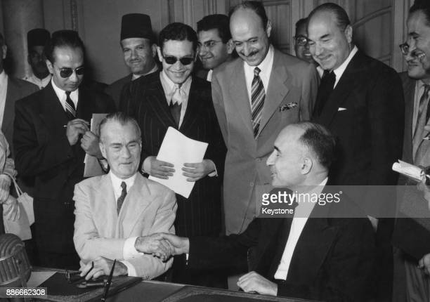 Jefferson Caffery the United States Ambassador in Cairo shakes hands with Dr Mahmoud Fawzi the Egyptian Minister of Foreign Affairs after signing the...