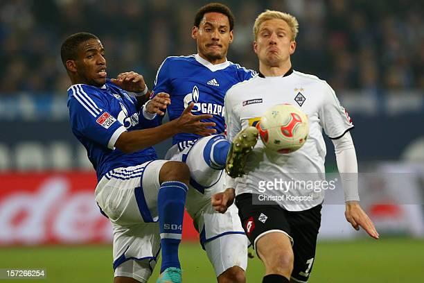 Jefferson Farfan and Jermaine Jones of Schalke challenge Mike Hanke of Moenchengladbach during the Bundesliga match between FC Schalke 04 and...