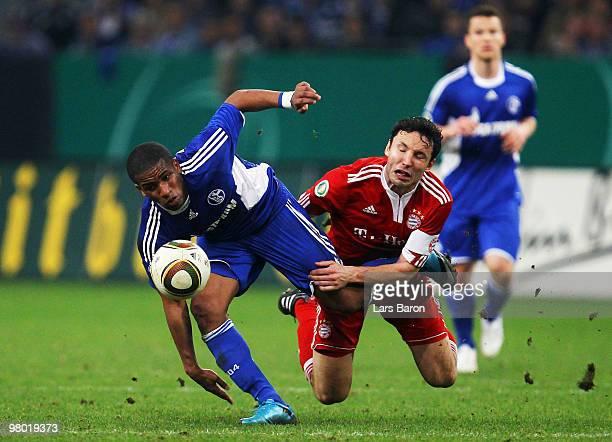 Jefferson Farfan of Schalke is challenged by Mark van Bommel of Muenchen during the DFB Cup semi final match between FC Schalke 04 and FC Bayern...