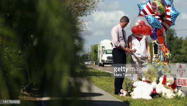 Jefferson Horwath and Kelly Lamoriello bow their heads next to a memorial to Trayvon Martin after leaving mementos outside The Retreat at Twin Lakes...