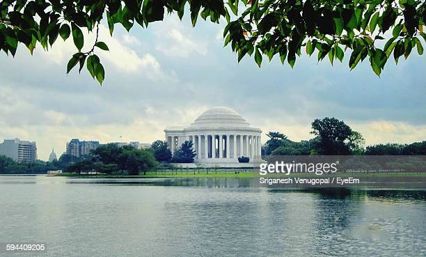 jefferson memorial by tidal basin against sky - jefferson memorial stock pictures, royalty-free photos & images