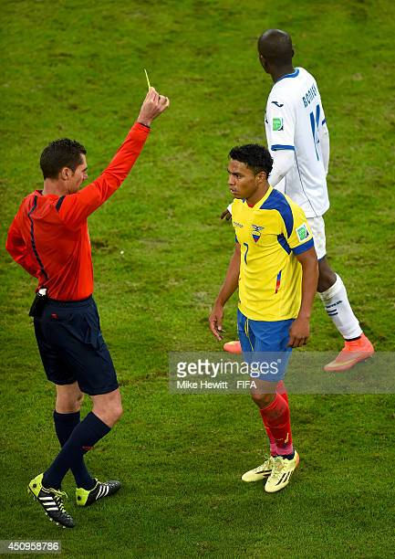 Jefferson Montero of Ecuador receives an yellow card from referee Benjamin Williams during the 2014 FIFA World Cup Brazil Group E match between...