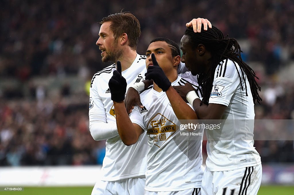 Jefferson Montero (C) of Swansea City celebrates scoring his team's first goal with his team mates Gylfi Sigurdsson (L) and Marvin Emnes (R) during the Barclays Premier League match between Swansea City and Stoke City at Liberty Stadium on May 2, 2015 in Swansea, Wales.