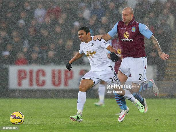 Jefferson Montero of Swansea City holds off Alan Hutton of Aston Villa during the Barclays Premier League match between Swansea City and Aston Villa...