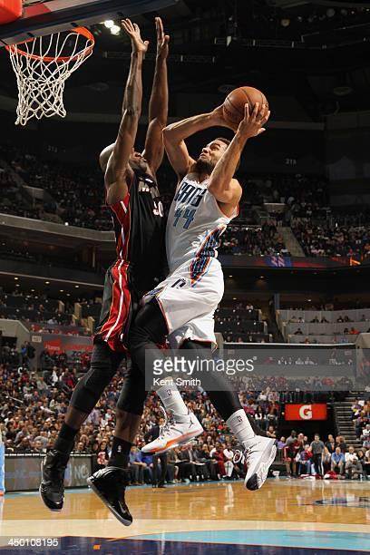 Jeffery Taylor of the Charlotte Bobcats shoots against Joel Anthony of the Miami Heat during the game at the Time Warner Cable Arena on November 16...