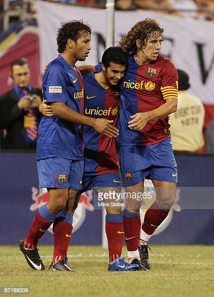 Jeffren Suarez of the FC Barcelona celebrates his goal in the 80th minute with teammate Pedrito and Carles Puyol against the New York Red Bulls at...