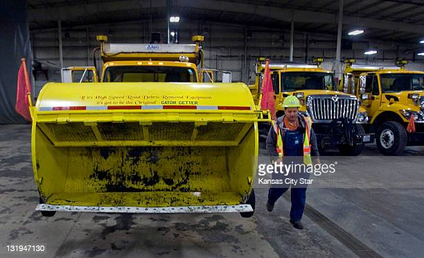 Jeffrey Brownsberger of the Missouri Department of Transportation walks by a truck outfitted with the Gator Getter that is used to pick up debris and...