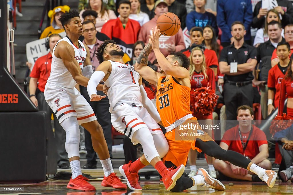 Jeffrey Carroll #30 of the Oklahoma State Cowboys is called for a charging foul against Brandone Francis #1 of the Texas Tech Red Raiders during the second half of the game on January 23, 2018 at United Supermarket Arena in Lubbock, Texas. Texas Tech defeated Oklahoma State 75-70.