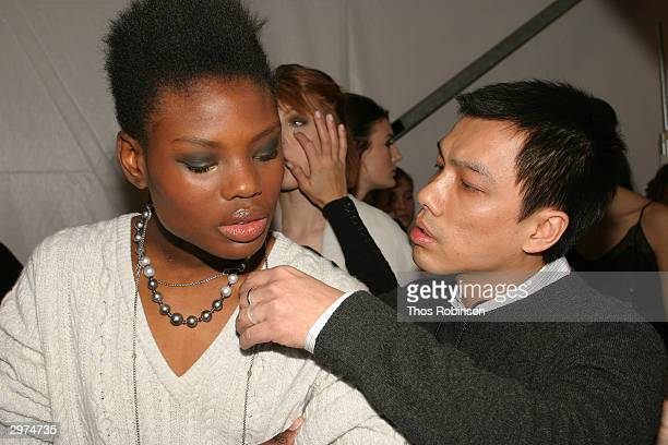 Jeffrey Chow helps a model get ready backstage at the Jeffrey Chow Fall 2004 during Olympus Fashion Week February 12 2004 in New York City