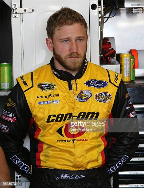 Jeffrey Earnhardt driver of the CanAm Ford stands in the garage area during practice for the NASCAR Sprint Cup Series FireKeepers Casino 400 at...