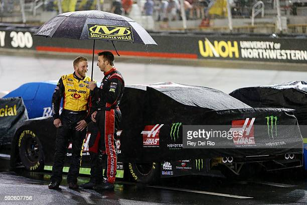 Jeffrey Earnhardt driver of the CanAm/Kappa Ford and Matt DiBenedetto driver of the Cosmo Motors Toyota talk underneath an umbrella during the NASCAR...