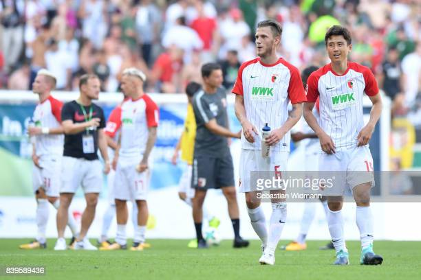 Jeffrey Gouweleeuw and JaCheol Koo of FC Augsburg walk on the pitch after the Bundesliga match between FC Augsburg and Borussia Moenchengladbach at...