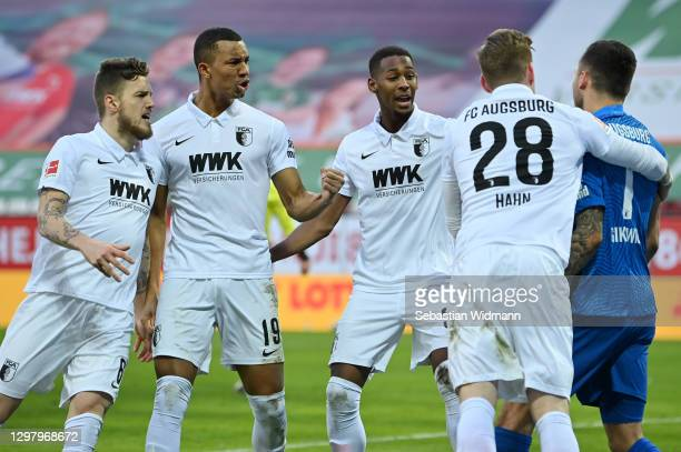 Jeffrey Gouweleeuw, Felix Uduokhai, Reece Oxford and Andre Hahn of Augsburg congratulate Rafal Gikiewicz of Augsburg after he saves a penalty during...
