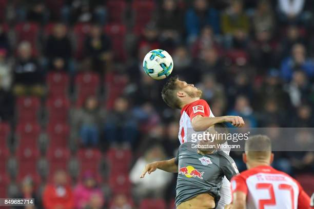 Jeffrey Gouweleeuw of Augsburg and Diego Demme of Leipzig jump for a header during the Bundesliga match between FC Augsburg and RB Leipzig at...