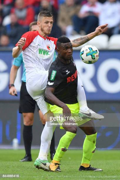 Jeffrey Gouweleeuw of Augsburg and Jhon Cordoba of Koeln compete for the ball during the Bundesliga match between FC Augsburg and 1 FC Koeln at...