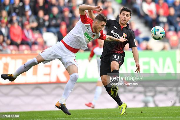 Jeffrey Gouweleeuw of Augsburg and Kevin Volland of Bayer 04 Leverkusen compete for the ball during the Bundesliga match between FC Augsburg and...