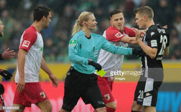 Jeffrey Gouweleeuw of Augsburg and Matthias Ginter of Moenchengladbach argue and Referee Bibiana Steinhaus intervenes with a yellow card during the...