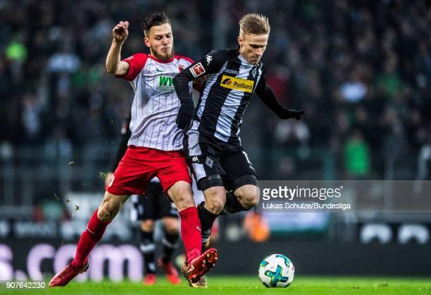 Jeffrey Gouweleeuw of Augsburg and Oscar Wendt of Moenchengladbach fight for the ball during the Bundesliga match between Borussia Moenchengladbach...
