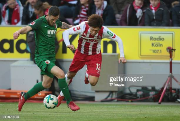 Jeffrey Gouweleeuw of Augsburg and Yuya Osako of Koeln battle for the ball during the Bundesliga match between 1 FC Koeln and FC Augsburg at...