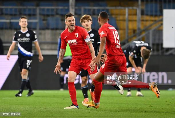 Jeffrey Gouweleeuw of Augsburg celebrates with Felix Uduokhai after scoring their team's first goal during the Bundesliga match between DSC Arminia...