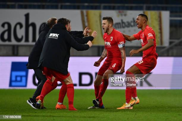 Jeffrey Gouweleeuw of Augsburg celebrates with Felix Uduokhai and team mates after scoring their team's first goal during the Bundesliga match...