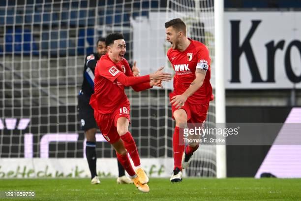 Jeffrey Gouweleeuw of Augsburg celebrates with Ruben Vargas after scoring his team's first goal during the Bundesliga match between DSC Arminia...