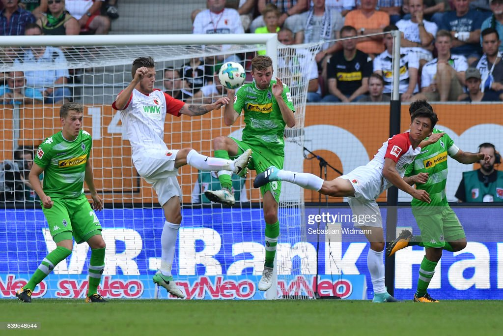 Jeffrey Gouweleeuw of Augsburg (2nd l), Christoph Kramer of Moenchengladbach (c) and Ja-Cheol Koo of Augsburg (r) fight for the ball during the Bundesliga match between FC Augsburg and Borussia Moenchengladbach at WWK-Arena on August 26, 2017 in Augsburg, Germany.