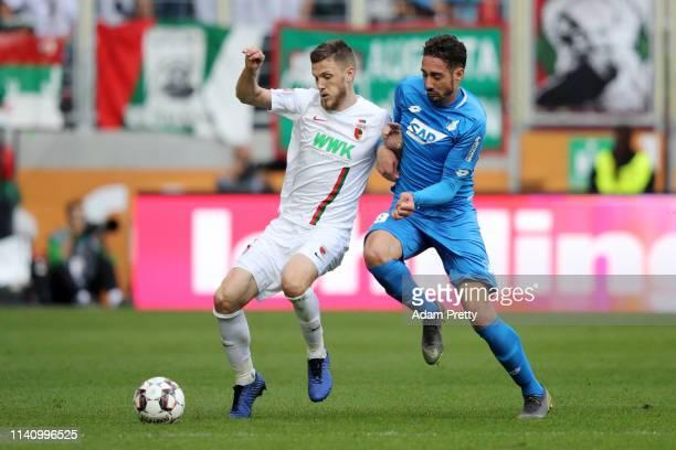 Jeffrey Gouweleeuw of Augsburg is challenged by Ishak Belfodil of 1899 Hoffenheim during the Bundesliga match between FC Augsburg and TSG 1899...
