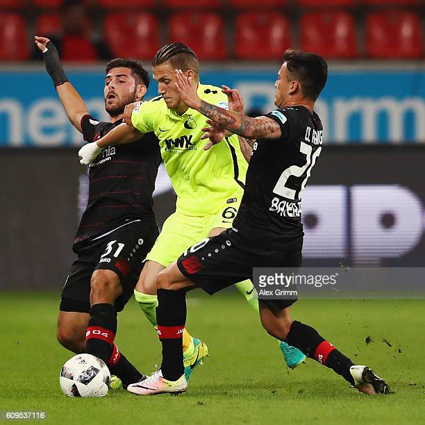Jeffrey Gouweleeuw of Augsburg is challenged by Kevin Volland and Charles Aranguiz of Leverkusen during the Bundesliga match between Bayer 04...
