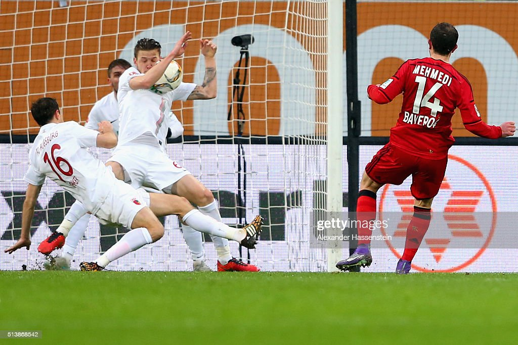 Jeffrey Gouweleeuw (C) of Augsburg plays the ball with the hand during the Bundesliga match between FC Augsburg and Bayer Leverkusen at WWK Arena on March 5, 2016 in Augsburg, Germany.
