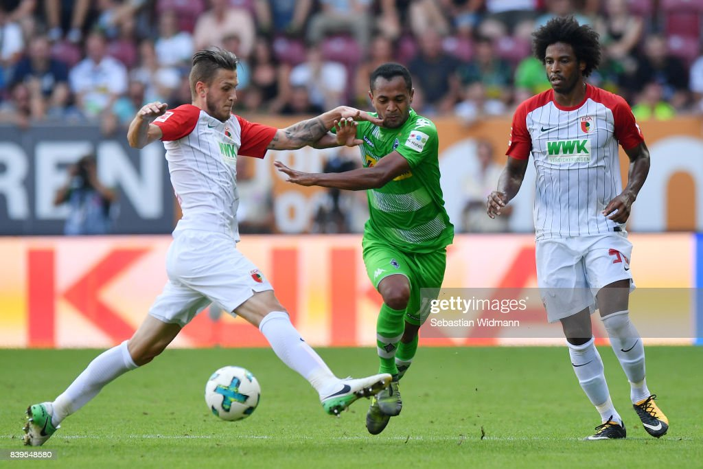 Jeffrey Gouweleeuw of Augsburg (l) Raffael of Moenchengladbach (c) and Caiuby of Augsburg during the Bundesliga match between FC Augsburg and Borussia Moenchengladbach at WWK-Arena on August 26, 2017 in Augsburg, Germany.