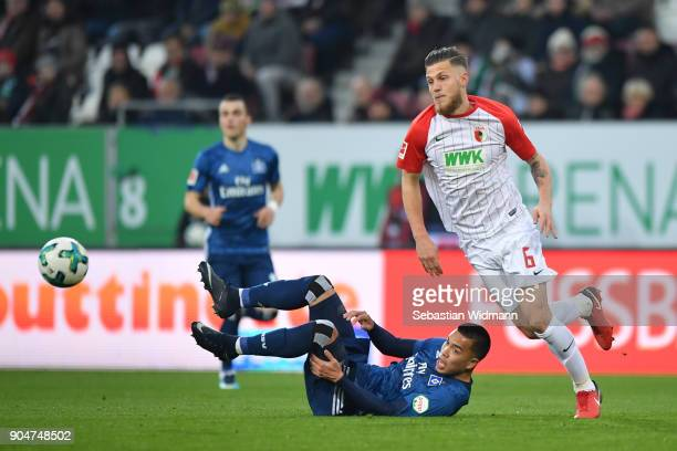 Jeffrey Gouweleeuw of Augsburg runs after the ball while Bobby Wood of Hamburg lies on the ground during the Bundesliga match between FC Augsburg and...