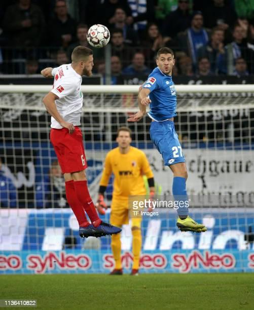 Jeffrey Gouweleeuw of FC Augsburg and Andrej Kramaric of TSG Hoffenheim battle for the ball during the Bundesliga match between TSG 1899 Hoffenheim...