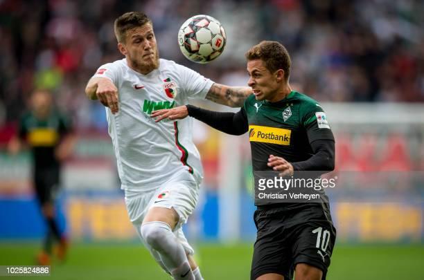Jeffrey Gouweleeuw of FC Augsburg and Thorgan Hazard of Borussia Moenchengladbach in action during the Bundesliga match between FC Augsburg and...