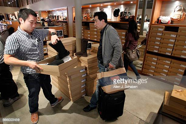 Jeffrey Hsu left a Mandarinspeaking sales associate with UGG helps Ding Sheng a tourist from China shop for his correct size of boot at the UGG store...