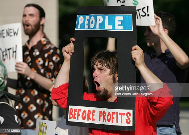 Jeffrey Jacoby carries a sign with other protesters outside the Meyerson Symphony Center in Dallas Texas Wednesday May 28 as Exxon Mobil Corporation...