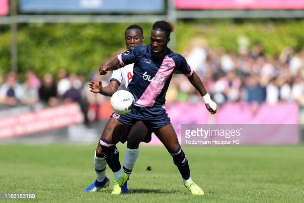Jeffrey Monakana of Dulwich Hamlet is challenged by Jubril Okedina of Tottenham Hotspur during the PreSeason Friendly match between Dulwich Hamlet...