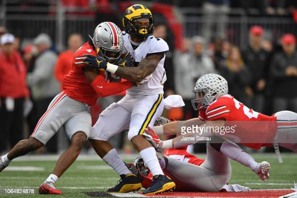 Jeffrey Okudah of the Ohio State Buckeyes hits Tarik Black of the Michigan Wolverines in the first quarter after a gain at Ohio Stadium on November...